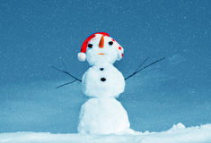 Hombre de la nieve en el casquillo de santa en la naturaleza Fotografía de archivo libre de regalías