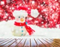 Hombre de la nieve sobre el fondo rojo y blanco borroso para la Navidad nueva Foto de archivo