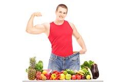 Hombre de la pérdida de peso que muestra sus músculos y situación detrás de una pila o fotos de archivo libres de regalías