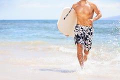 Hombre de la persona que practica surf de la diversión de la playa que corre con bodyboard Imagen de archivo libre de regalías