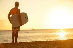 Hombre de la persona que practica surf en la playa en la puesta del sol que sostiene bodyboard Fotos de archivo