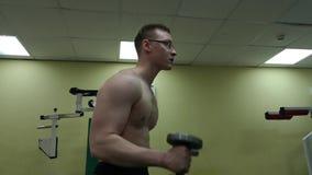 Hombre de la pesa de gimnasia en el levantamiento de pesas de la aptitud del bíceps del entrenamiento del gimnasio metrajes