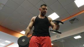 Hombre de la pesa de gimnasia en el levantamiento de pesas de la aptitud del bíceps del entrenamiento del gimnasio almacen de metraje de vídeo