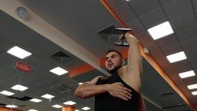 Hombre de la pesa de gimnasia en el levantamiento de pesas de la aptitud de las manos del entrenamiento del gimnasio almacen de metraje de vídeo