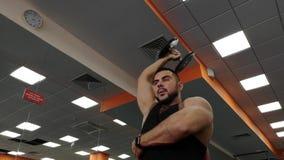 Hombre de la pesa de gimnasia en el levantamiento de pesas de la aptitud de las manos del entrenamiento del gimnasio almacen de video