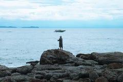 Hombre de la pesca en el océano azul | vacaciones de verano al aire libre Imágenes de archivo libres de regalías