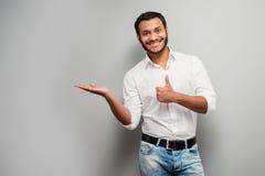Hombre de la raza mixta que señala a un lado con el pulgar para arriba Imagen de archivo