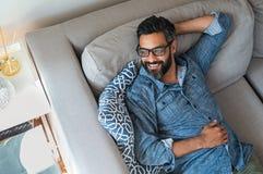 Hombre de la raza mixta que se relaja en el sofá fotografía de archivo