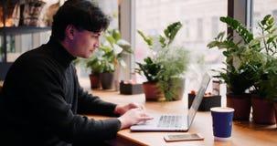 Hombre de la raza mixta que trabaja con el ordenador portátil y el teléfono elegante en el café metrajes