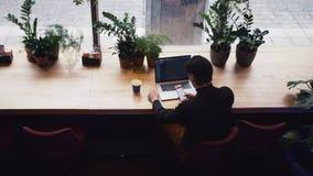 Hombre de la raza mixta que trabaja con el ordenador portátil y el teléfono elegante en el café almacen de video