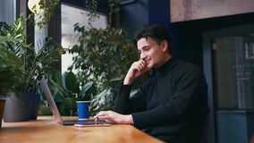 Hombre de la raza mixta que trabaja con el ordenador portátil y el teléfono elegante en el café almacen de metraje de vídeo