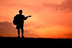 Hombre de la silueta con la guitarra Foto de archivo libre de regalías