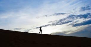 Hombre de la silueta que camina abajo de desierto con las nubes Imagen de archivo libre de regalías