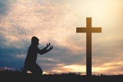 Hombre de la silueta que ruega con la cruz Imagen de archivo