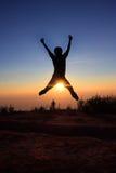 Hombre de la silueta que salta sobre el sol Fotos de archivo libres de regalías