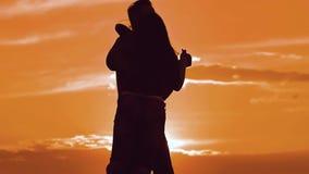 Hombre de la silueta y muchacha de un baile lento joven feliz de la pareja de matrimonios afuera en la puesta del sol Pares gozan almacen de video