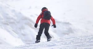 Hombre de la snowboard en el piste aplanado - cuesta imagen de archivo libre de regalías