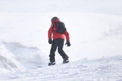 Hombre de la snowboard en el piste aplanado - cuesta fotos de archivo