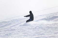 Hombre de la snowboard en el piste aplanado - cuesta imagen de archivo