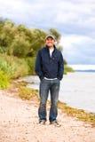 Hombre de la sonrisa de los jóvenes en la costa del río foto de archivo