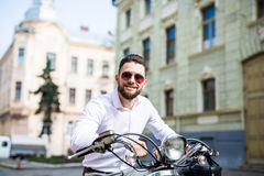 Hombre de la sonrisa de los jóvenes en las gafas de sol que montan la vespa a lo largo de la ciudad de la calle Imagen de archivo