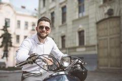 Hombre de la sonrisa de los jóvenes en las gafas de sol que montan la vespa a lo largo de la ciudad de la calle entonado Fotos de archivo