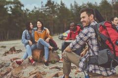 Hombre de la sonrisa que se sienta con sus amigos al aire libre fotos de archivo libres de regalías
