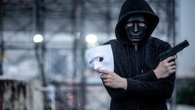 Hombre de la sudadera con capucha del misterio que sostiene la máscara y el arma blancos imágenes de archivo libres de regalías