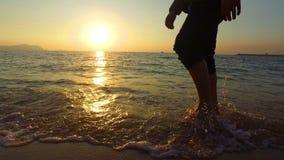 hombre de la toma panorámica 4K que corre en el mar bajo en la puesta del sol metrajes