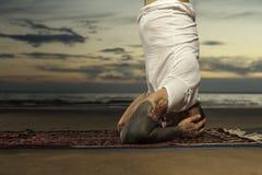 Hombre de la yoga que hace actitud del headstand en la playa fotos de archivo