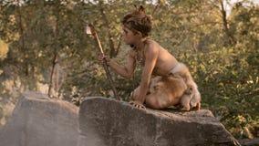 Hombre de las cavernas, muchacho de hombres con el arma primitiva al aire libre Guerrero prehistórico antiguo metrajes