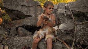 Hombre de las cavernas, muchacho de hombres que hace el arma de piedra primitiva en campo almacen de video