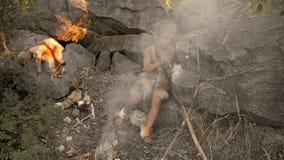 Hombre de las cavernas, muchacho de hombres que hace el arma de piedra primitiva en campo almacen de metraje de vídeo