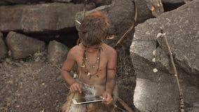 Hombre de las cavernas, muchacho de hombres que hace usando la tableta metrajes