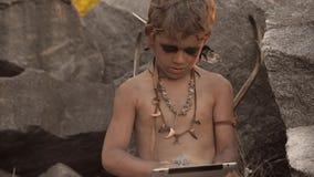 Hombre de las cavernas, muchacho de hombres que hace usando la tableta almacen de video