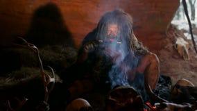 Hombre de las cavernas prehistórico con la tableta en cueva almacen de metraje de vídeo