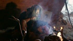 Hombre de las cavernas prehistórico que usa el ordenador portátil almacen de metraje de vídeo