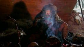 Hombre de las cavernas prehistórico que usa la tableta almacen de video