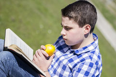 Hombre de Looking.Young que lee un libro en al aire libre con la manzana amarilla. Fotos de archivo