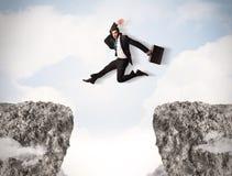 Hombre de los asuntos divertidos que salta sobre rocas con hueco Imagen de archivo libre de regalías