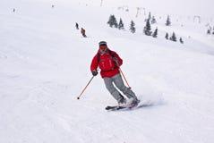 Hombre de los esquiadores de Alpen que se ejecuta abajo contra los elevadores Imagen de archivo libre de regalías