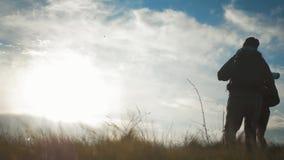 Hombre de los pares y turista felices de la mujer en la parte superior de la monta?a en la puesta del sol al aire libre durante u metrajes