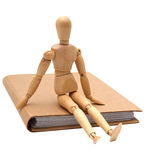 Hombre de madera que se sienta en el cuaderno marrón fotografía de archivo libre de regalías