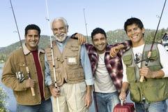 Hombre de mediana edad con tres hijos en viaje de pesca Foto de archivo libre de regalías