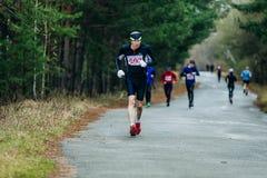 Hombre de mediana edad del corredor que corre abajo del camino en parque Fotos de archivo
