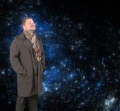 Hombre de mediana edad en una capa que mira para arriba en fondo estrellado del universo Fotos de archivo libres de regalías