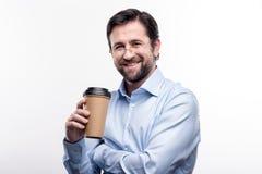 Hombre de mediana edad encantador en las lentes que presentan con la taza de café Foto de archivo