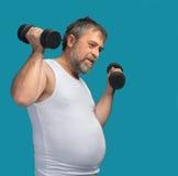Hombre de mediana edad gordo que ejercita con pesas de gimnasia fotos de archivo libres de regalías
