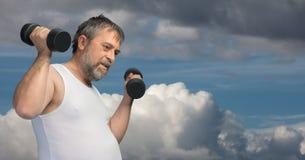 Hombre de mediana edad gordo que ejercita con pesas de gimnasia fotografía de archivo