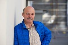 Hombre de mediana edad hermoso que presenta en la chaqueta azul que inclina la pared gris Retrato masculino al aire libre Fotografía de archivo